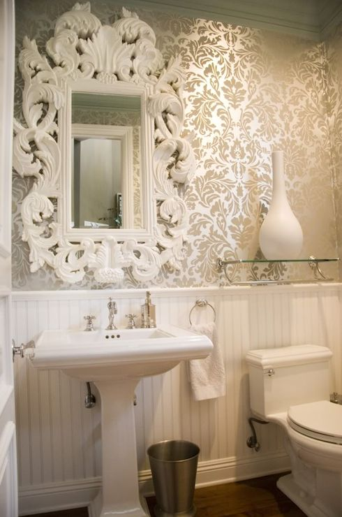 Stunning powder room with white beadboard lower wall and golden metallic damask wallpapered upper wall. The bathroom features a traditional style pedestal sink paired with a ornate white Baroque mirror. Beside the sink hangs a nickel towel ring and nickel wastebasket. Over the toilet hangs a glass shelf holding a large white vase. decorpad.com