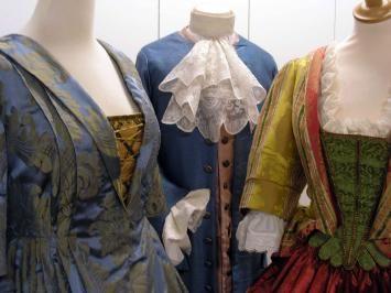 De blauwe japon à la Francaise heeft achter een pli Watteau. De gele japon bestaat uit een mantua en onderrok met een groen borststukje. Onder beide japonnen een hemd met kanten manchetten en halsruche. Het herenkostuum is een Habit à la Francaise.