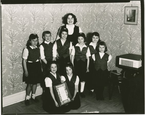 1957/58 A troop of girls belonging to the Blue Birds (Camp Fire Girls) stands and kneels with a framed poster. The girls are in uniform, some complete with beanie caps with blue bird emblem. Troop leader stands in back. See also mcalA14F16i12 under Portraits, children, unidentified