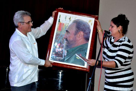 Consuelo Baeza, integrante del secretariado nacional de la CTC, entregó un cuadro con la imagen del Comandante en Jefe Fidel Castro a René González Barrios, presidente del IHC. Foto: Eddy Martin Díaz