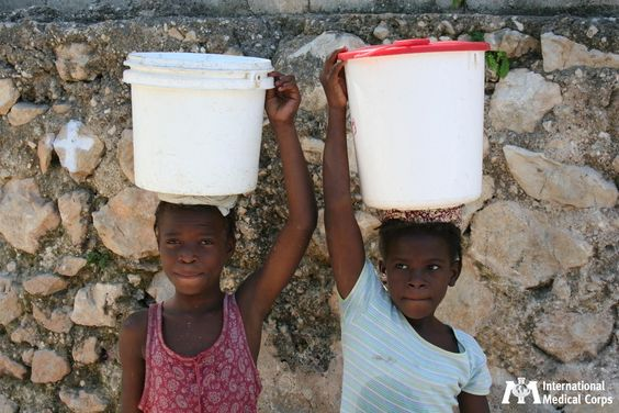 October 29: Two girls balance buckets of water on their heads in Haiti. Photo: International Medical Corps Staff, Haiti 2012: