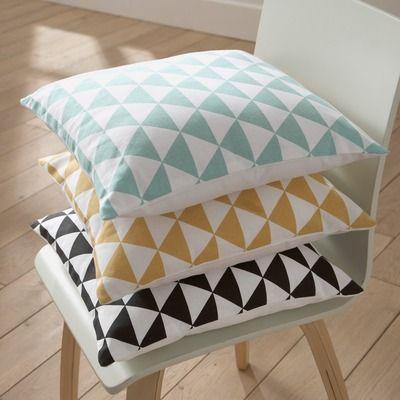 Coussins scandinaves à motifs géométriques posés sur une chaise