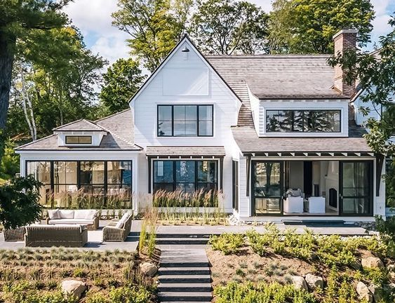 The Exterior Of This House Featuring White Siding Tin Roofs Barn Lighting And The Touches Of Th Dream House Exterior Modern Farmhouse Exterior House Exterior