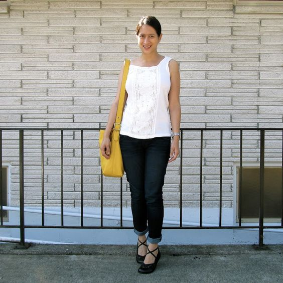 white top, dark blue skinny jeans, yellow bag, ballet flats