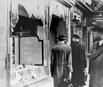 Pedestrians walk past a burnt-out Jewish shop in Berlin in 1938, the day after the Kristallnacht. They and the world watched.