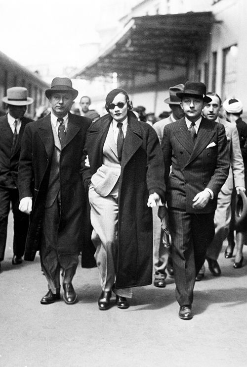 Marlene Dietrich with her husband, Rudolf Sieber, at a train station in Paris. Both arrived from Hollywood, May 20th, 1930: gdfalksen.com: