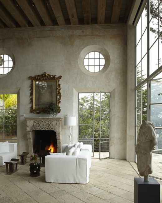 Best French country farmhouse decor in a magnificent farmhouse living room with white decor, round windows, and limestone fireplace. #frenchfarmhouse #frenchcountry #livingroom #rusticdecor #Provence