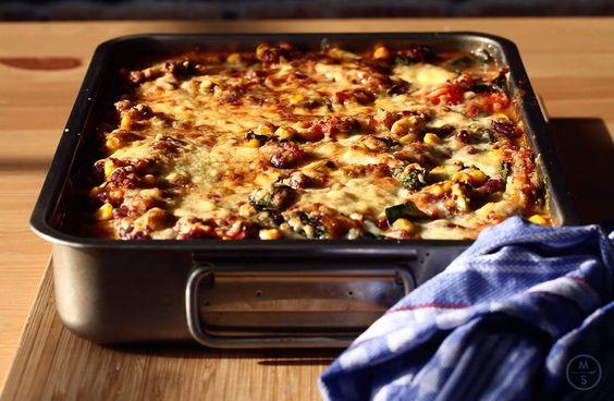 Zo maak je het: • 1 avocado en 1 rode paprika in stukjes snijden en met 200 gram gekookte rode quinoa vermengen • 1 blik maïs, 1 blik kidneybonen met sap en 1 blik tomatenblokjes toevoegen • Kruiden met verse koriander, 1tl komijn, 1el gerookte paprikapoeder, zout en peper • Op 220ºC voor 10 min bakken in de oven, dan bestrooien met kaas en op de grillfunctie nog 2-3 min gratineren  Direct uit de oven serveren & genieten