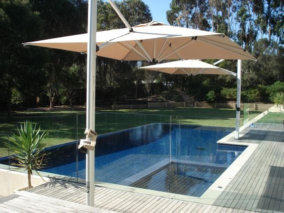 Two square cantilever umbrellas providing great shade coverage over a pool