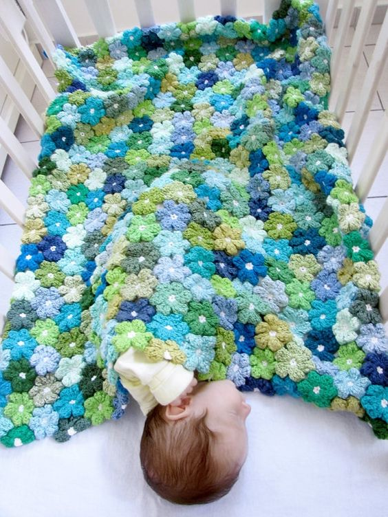 Beautiful baby blanket made from individual crocheted flowers that are then joined together. Good family project.