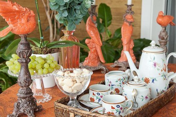 mesa de chá da tarde em tons terrosos com set de chá com estampa floral. Pássaros de louça em terracota.
