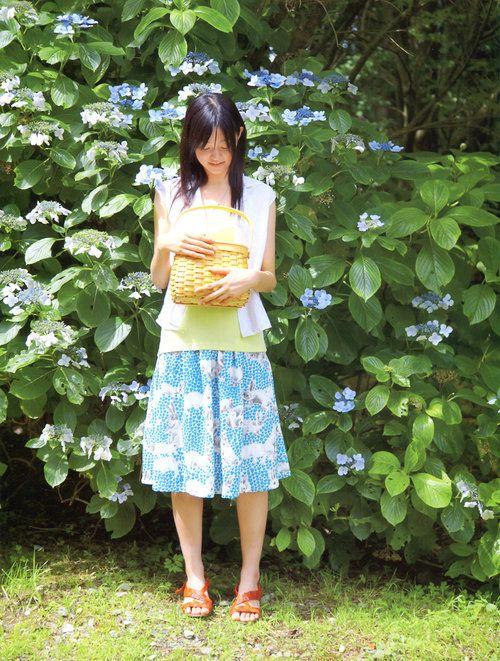 アジサイの前に立っているスカートをはいた小林涼子の画像