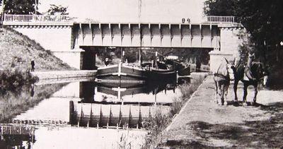 Une péniche chargée monte à Roanne et passe sous le pont-rivière de l'Oudan, halée par deux mulets. (carte postale ancienne).