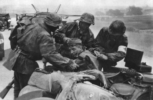 Soldiers and a medic from 3rd SS Panzer Division Totenkopf helping a wounded comrade.