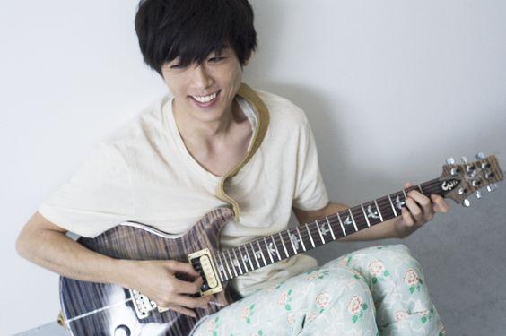 白いシャツを着てギターを持っている高橋一生の画像