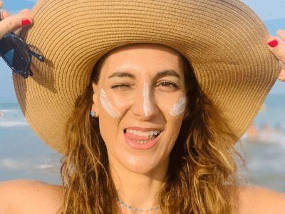 una chica con crema de sol en el rostro y un gorro. En la playa