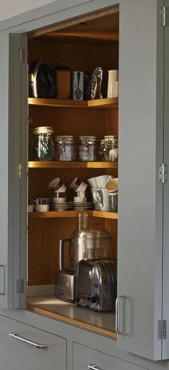 Grey bi-fold kitchen cupboard doors reveal wooden shelving inside a larder cupboard for food and appliance storage. Kitchen designed for Figura