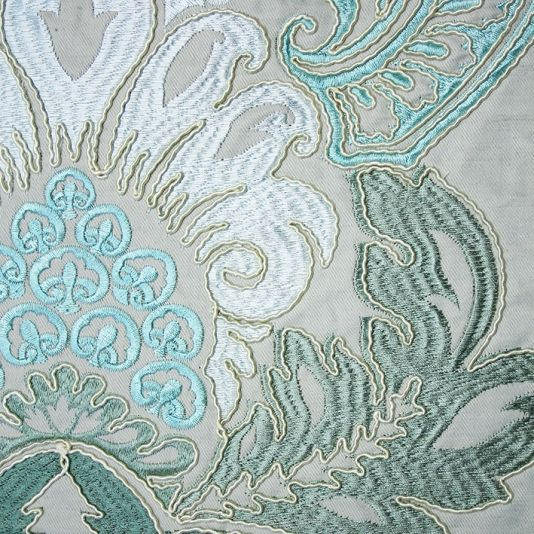 Waterford Damask Fabric An elegant damask fabric with ornate cushion embroidery creating a three dimensional effect in aqua, sage, turquoise, gold and powder blue on a grey background.