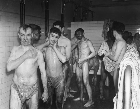 9th December 1938: Miners having a shower at Woodlark Colliery, Bardsley, Ashton-under-Lyne. (Photo by Fox Photos/Getty Images)