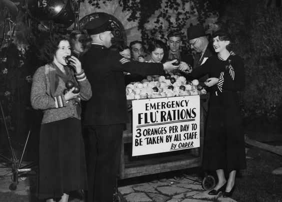 Past Flu Remedies:  Under the advice everyone should eat three oranges a day, gratefully accept your vitamin C 'rations' (1940) (Getty)