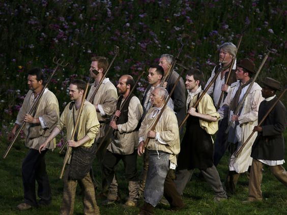 Performers hold farm tools during the pre-show of the opening ceremony of the London 2012 Olympic Games.