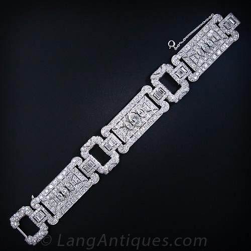 This magnificent, opulent and glamorous platinum and diamond bracelet hails from the peak of the high-Art Deco period, circa 1925. This exceptional jewel is comprised of three 3/4 inch wide articulated geometric plaques, each of which centers upon three sparkling old European-cut marquise diamonds with the center marquise weighing 1.50 carats. The marquises are presented against a sparkling background of European-cut diamonds. The three main sections are connected by gorgeous 7/8 in...