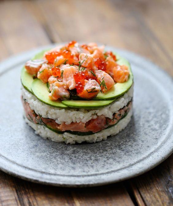 Sushi cake au saumon - 400 gr de riz à sushis, 3-4 cs vinaigre de riz, 1,5 cs sucre, sel, 8 feuilles d'algue nori, 650 gr de saumon cru, 30 gr d'oeufs de truite, aneth, 2 avocats, 1 concombre, 2 citrons verts, 1 cs huile d'olive.