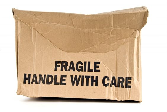 Fragile Handle With Care brown box crushed.  On white background: