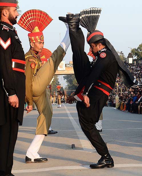 "Wagah, Pakistan — Pakistani Rangers (in black) and Indian Border Security Force personnel (in brown) perform a ""flag off"" ceremony on the Pakistan-India border."