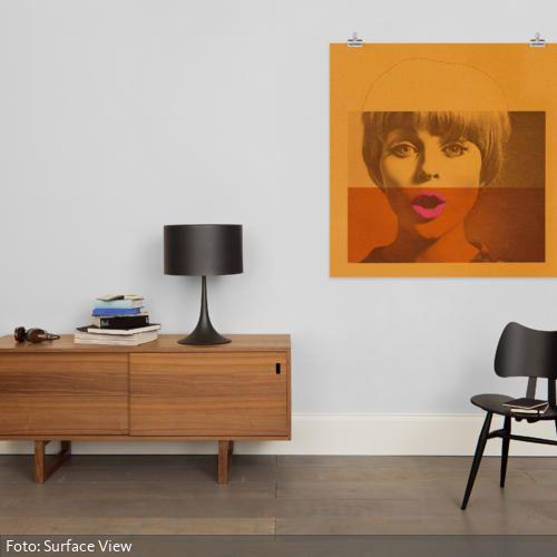 Cool und modern: An der grauen Wand kann die Pop-Art-Skizze auf der Leinwand besonders gut hervortreten. Das auffällige Orange und die Rottöne des Wandbildes sind hierbei ausreichend, um das schlichte Grau der Wand und des dunklen Holzbodens auszugleichen.