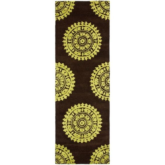 This contemporary New Zealand wool rug features a comfortable 0.5-inch pile which is soft against your tired feet. Handmade, this runner features a geometric design in vibrant greens and a rich brown background, perfect in any decor.