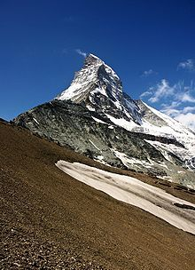 The Matterhorn  is a mountain in the Pennine Alps on the border between Switzerland and Italy. Its summit is 4,478 metres (14,690 ft) high, making it one of the highest peaks in the Alps.[2] The four steep faces, rising above the surrounding glaciers, face the four compass points. The mountain overlooks the town of Zermatt in the canton of Valais to the north-east and Breuil-Cervinia in the Aosta Valley to the south.