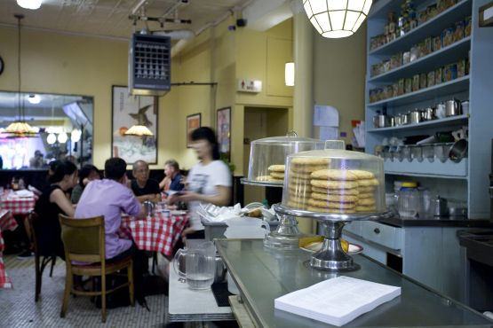 "Nom Wah Tea Parlor. NY's first dim sum house opened in 1920 at a crook in Doyers Street known at the time as ""the bloody angle."" That Chinatown passage bore witness to the grisly havoc of the Tong gang wars—shootings and hatchet murders—but the bakery and tea shop had a sweeter reputation: Its almond cookies and moon cakes were legendary."
