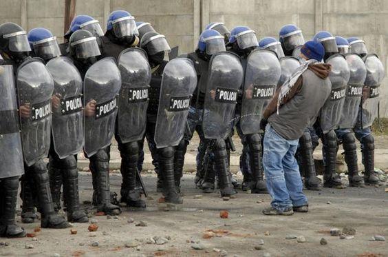 Yo contra el mundo. Un manifestante orina delante de una fila de agentes de policía en San Carlos de Bariloche, Argentina.: