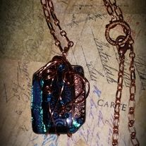 """Handcrafted Dichroic pendant in teal and copper colors. Wire wrapped in copper and accented with teal seed beads.    Such a unique necklace!  Pendant measure 1.75""""x 1"""" and hands from a 20 inch copper chain with a lobster clasp closure.    A bright and vibrant necklace!."""