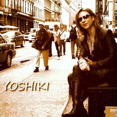 サングラスをかけて街中に座っているXJAPAN・YOSHIKIの画像