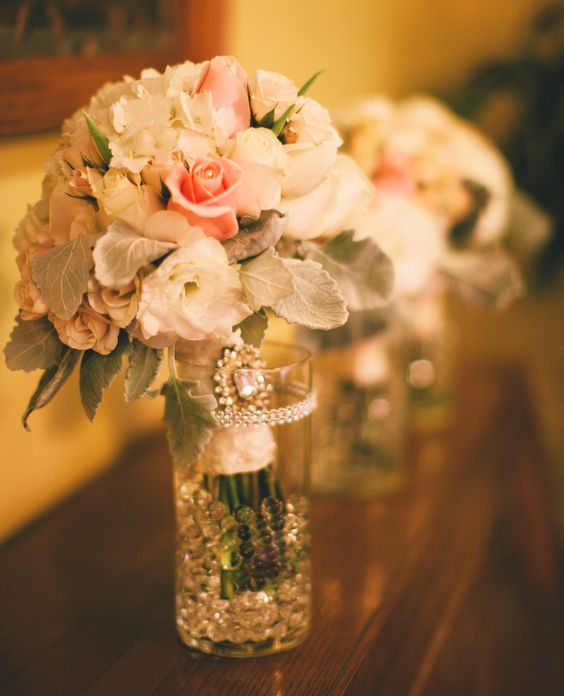 White & blush roses with dusty miller. stems wrapped in French lace, studded with pearls and adorned with rhinestone brooch.
