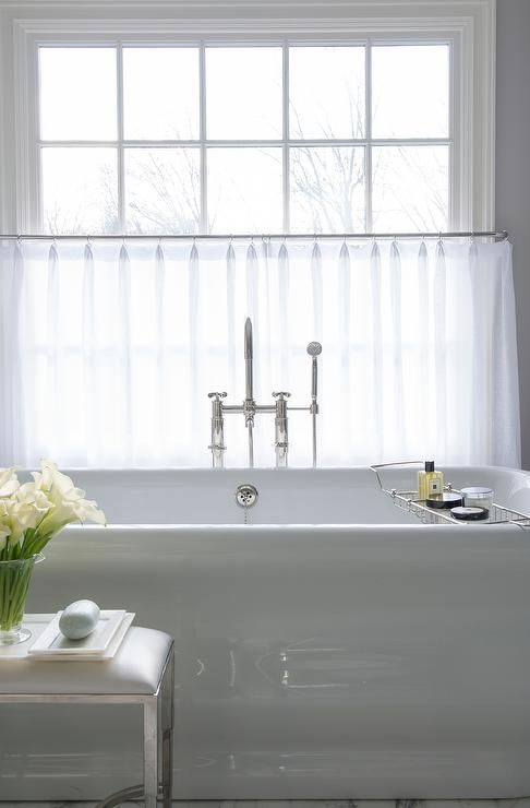Sophisticated bathroom features a Waterworks Empire Freestanding Tub and Easton Metal Vinyl Stool placed under windows dressed in white cafe curtains.: