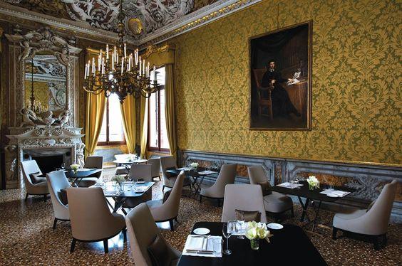 Yellow Dining Room do Palazzo Papadopoli, em Veneza, na Itália, que se tornou um hotel na prancheta do escritório Denniston Architects. O mobiliário contemporâneo sugerido em projeto não interfere nos elementos originais como o lustre e o papel de parede.