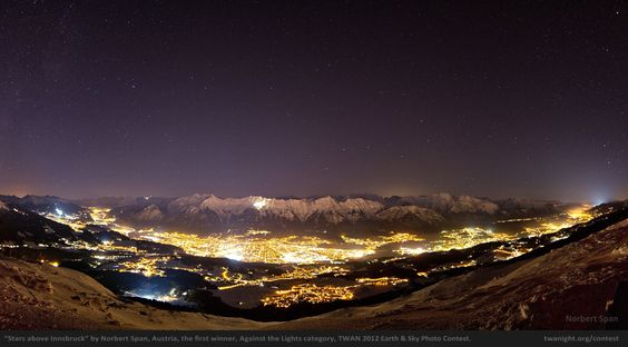 """The World At Night 2012 Contest. The first prize in the Against the Lights category goes to Norbert Span for his photo """"Stars above Innsbruck"""". The panoramic image shows the northern stars above the lights of Innsbruck, a city embraced by the Alps in Austria."""