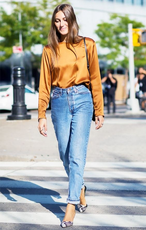 Giorgia Tordini wears a silk blouse, high-waisted jeans, and snakeskin flats