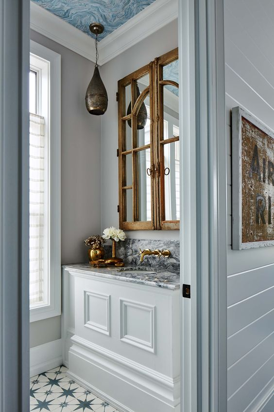 Eclectic home decor with blue and marble counter in a powder room bath designed by Sarah Richardson