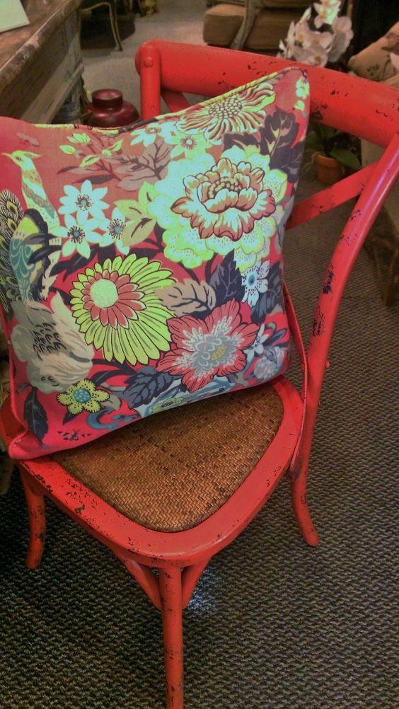 Coral colored chair with matching print pillow.