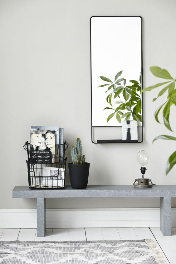 Horizontal mirror with shelf in a sleek metal frame accompanied by a concrete bench from our 2017 collection.