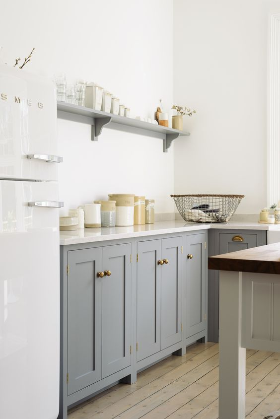 Beautifully simple deVOL Shaker cupboards with brass door furniture and sleek 'Lagoon' Silestone worktops, a white Smeg fridge, a few vintage pots and some lovely linens. #silestone #lagoon #quartzcountertops