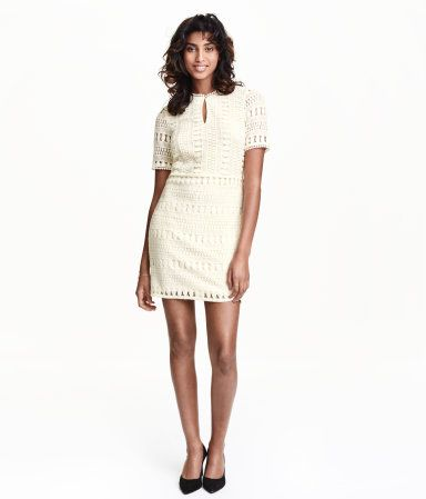 Natural white. Short dress in lace. Lined at front and back, buttons at top, short sleeves, and seam at waist.