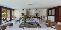 Casa de praia rústica tem ambientes integrados e madeira