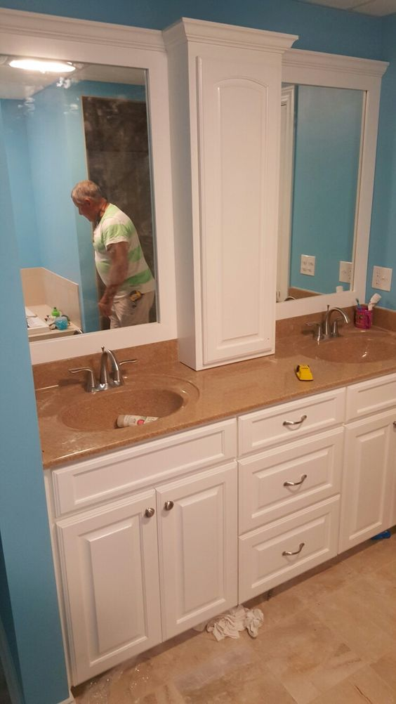 White painted maple vanity with centered medicine cabinet .