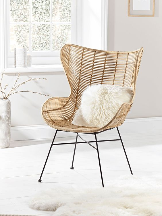 Woven from flat rattan with a strong metal frame, our large elegant chair has a wide seat curved, high winged back and low arms. Inspired by Scandi living, it features blonde, open weave rattan details and black iron legs. The perfect occasional chair for your living space or bedroom, team this comfortable seat with something from our Sheepskins & Hides collection to complete the look.