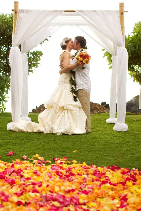 Love this simple archway with #bright #tropical petals www.makenaweddings.com